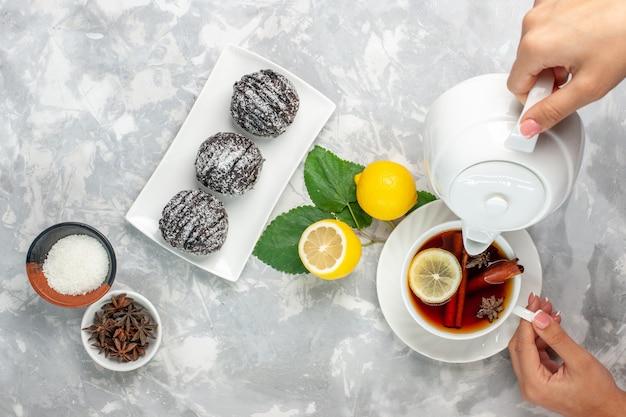 Vista superior deliciosos bolos de chocolate redondos pequenos formados com limão e xícara de chá na superfície branca clara bolo de frutas biscoito doce açúcar assar biscoito