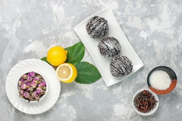 Vista superior deliciosos bolos de chocolate redondos pequenos formados com limão na superfície branca bolo de frutas biscoito doce açúcar