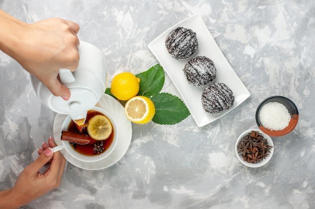 Vista superior deliciosos bolos de chocolate redondos pequenos formados com limão na superfície branca-clara bolo de frutas biscoito doce açúcar assar biscoito