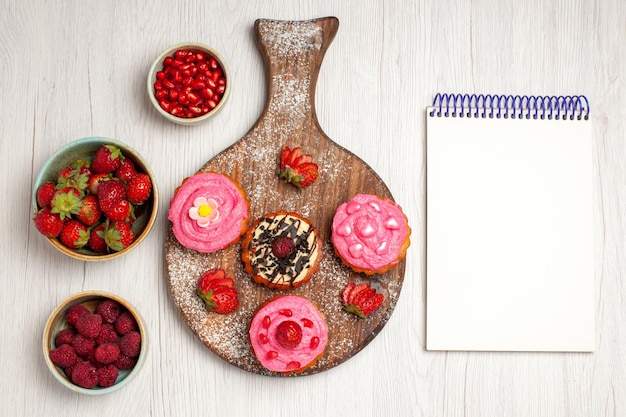 Vista superior deliciosos bolos de frutas sobremesas cremosas com frutas e frutas no fundo branco creme chá doce biscoito sobremesa bolo