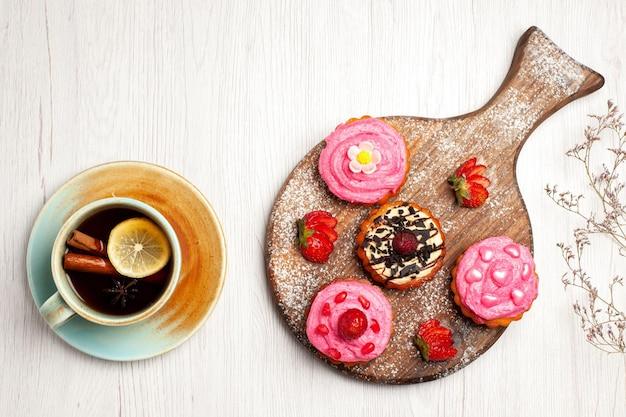 Vista superior deliciosos bolos de frutas, sobremesas cremosas com frutas e uma xícara de chá no fundo branco creme chá doce sobremesa bolo biscoito