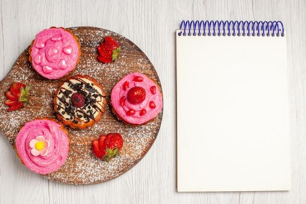 Vista superior deliciosos bolos de frutas sobremesas cremosas com frutas no fundo branco creme chá sobremesa biscoito bolo biscoito