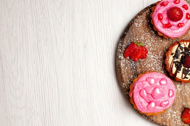 Vista superior deliciosos bolos de frutas sobremesas cremosas com frutas no fundo branco doce creme chá sobremesa biscoito bolo torta cookie