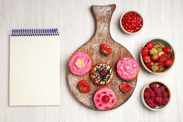 Vista superior deliciosos bolos de frutas, sobremesas cremosas com frutas vermelhas e frutas em um fundo branco creme biscoito doce sobremesa bolo chá