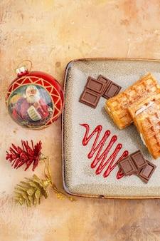 Vista superior deliciosos bolos de waffle com barras de chocolate no fundo marrom