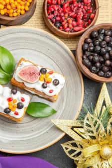 Vista superior deliciosos bolos de waffle com frutas frescas em um fundo escuro
