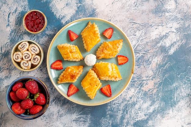 Vista superior deliciosos bolos doces com frutas em fundo azul