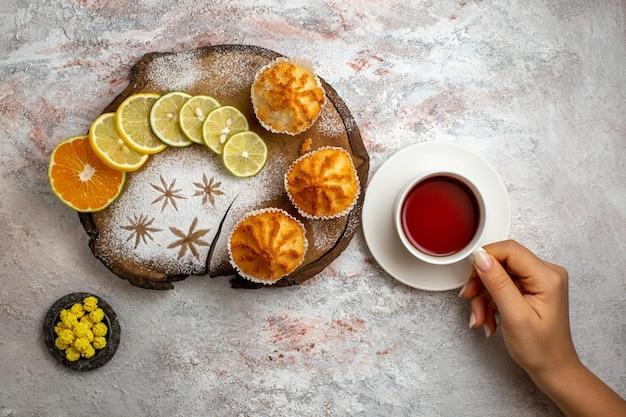 Vista superior deliciosos bolos doces com rodelas de limão e uma xícara de chá na superfície branca