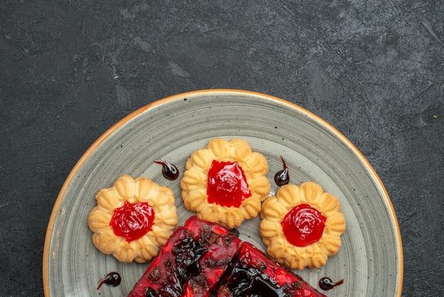 Vista superior deliciosos bolos doces de frutas com biscoitos em fundo escuro biscoitos de chá torta de biscoito bolo doce