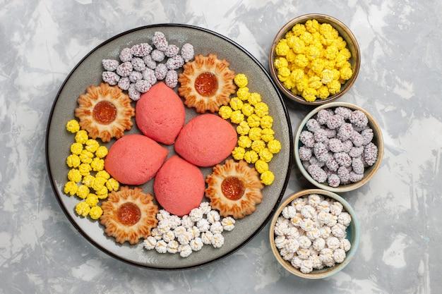 Vista superior deliciosos bolos rosa com doces e biscoitos na superfície branca