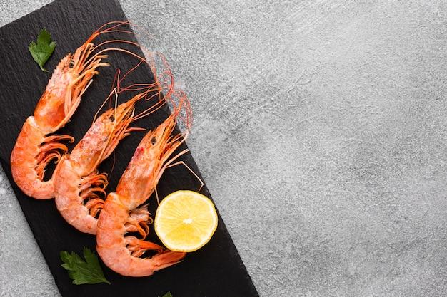 Vista superior deliciosos camarões com limão no prato
