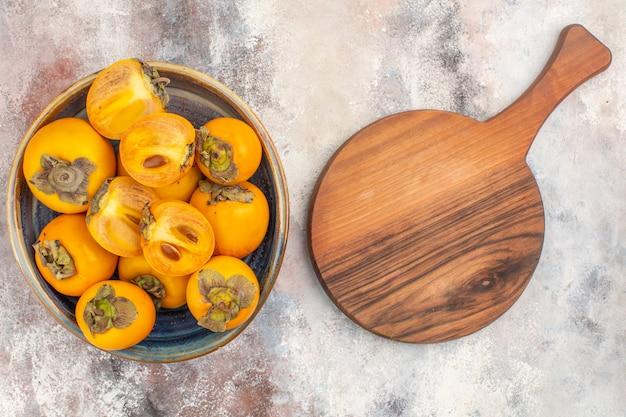 Vista superior deliciosos caquis em caixa de madeira redonda e uma tábua de corte em fundo nude