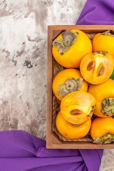 Vista superior deliciosos caquis em um xale roxo de caixa de madeira em fundo nude