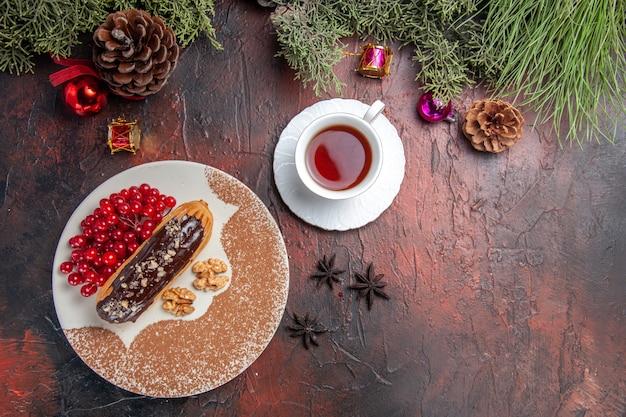 Vista superior deliciosos choco eclairs com frutas e chá na mesa escura torta torta sobremesa doce