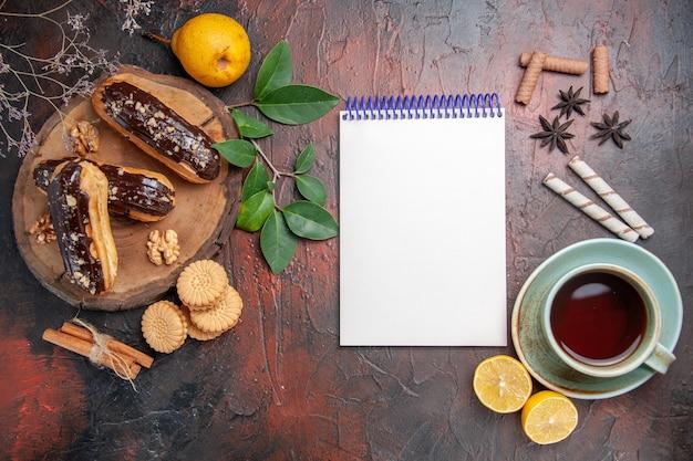 Vista superior deliciosos choco eclairs com uma xícara de chá na mesa escura sobremesa doce bolo