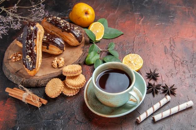 Vista superior deliciosos choco eclairs com uma xícara de chá no chão escuro, sobremesa, bolo doce