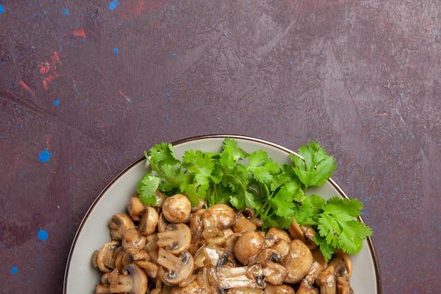 Vista superior deliciosos cogumelos cozidos com verduras em um fundo escuro.