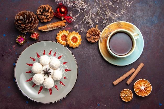 Vista superior deliciosos doces de coco com uma xícara de chá no fundo escuro chá doce biscoito bolo doce bombom