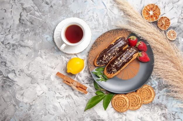 Vista superior deliciosos eclairs de chocolate com uma xícara de chá em um biscoito de sobremesa de bolo branco claro