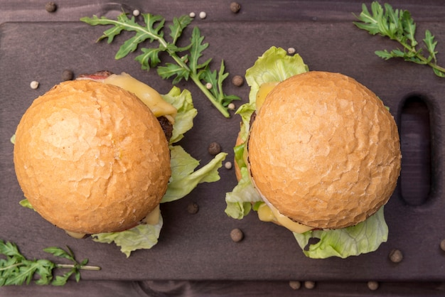 Vista superior deliciosos hambúrgueres na mesa escura