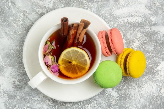 Vista superior deliciosos macarons franceses bolos coloridos com uma xícara de chá na superfície branca