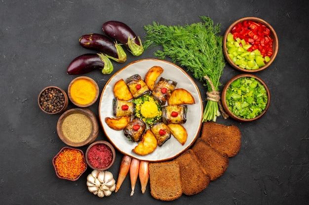 Vista superior deliciosos pãezinhos de berinjela cozidos, prato com batatas e pães no fundo escuro, cozinhando comida, batata frita, assar