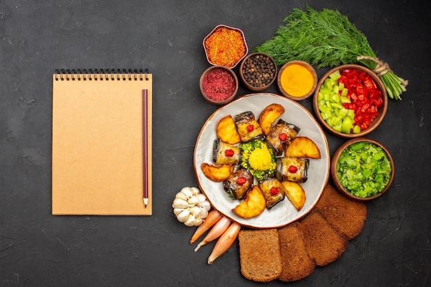 Vista superior deliciosos pãezinhos de berinjela cozidos, prato com batatas e pães no fundo escuro, cozinhando prato de comida assar batata frita