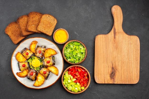 Vista superior deliciosos pãezinhos de berinjela prato cozido com batatas assadas e pão no fundo escuro prato cozinhar comida batata frita assar