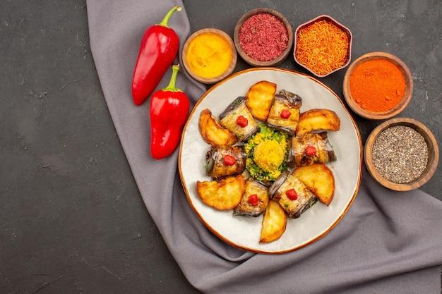 Vista superior deliciosos pãezinhos de berinjela, prato cozido com batatas assadas e temperos em fundo escuro