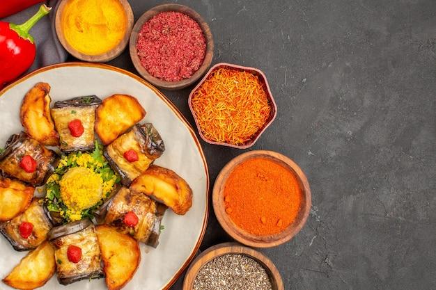 Vista superior deliciosos pãezinhos de berinjela, prato cozido com batatas assadas e temperos na mesa escura.