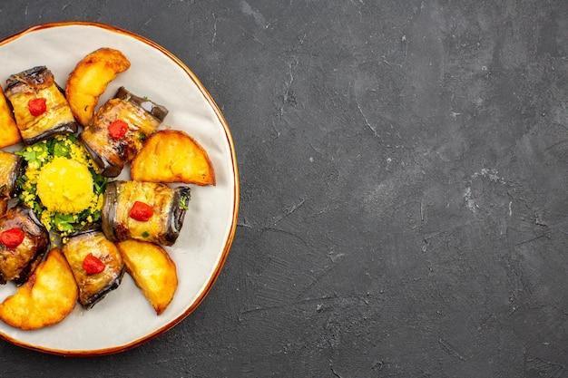 Vista superior deliciosos pãezinhos de berinjela prato cozido com batatas assadas no chão escuro prato de refeição cozinhando comida assar batata frita