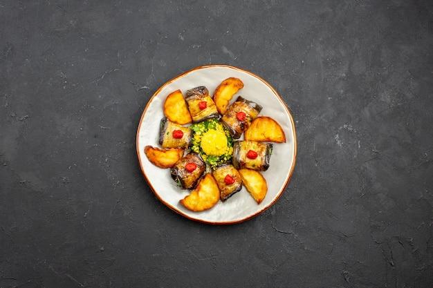 Vista superior deliciosos pãezinhos de berinjela prato cozido com batatas assadas no fundo escuro prato de refeição cozinhando comida assar batata frita