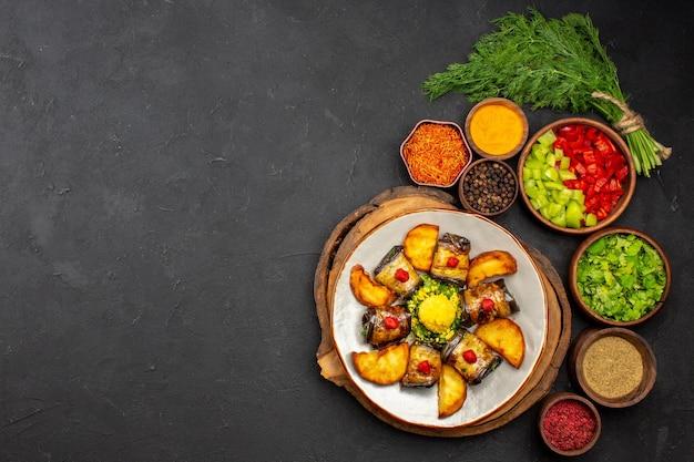 Vista superior deliciosos pãezinhos de berinjela, prato cozido com batatas e diferentes temperos na superfície escura prato refeição jantar