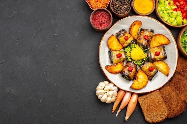 Vista superior deliciosos pãezinhos de berinjela, prato cozido com batatas e pães na mesa escura, cozinhando prato de fritura assar batata