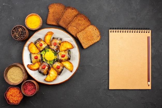 Vista superior deliciosos pãezinhos de berinjela prato cozido com batatas, pão e temperos em fundo escuro.