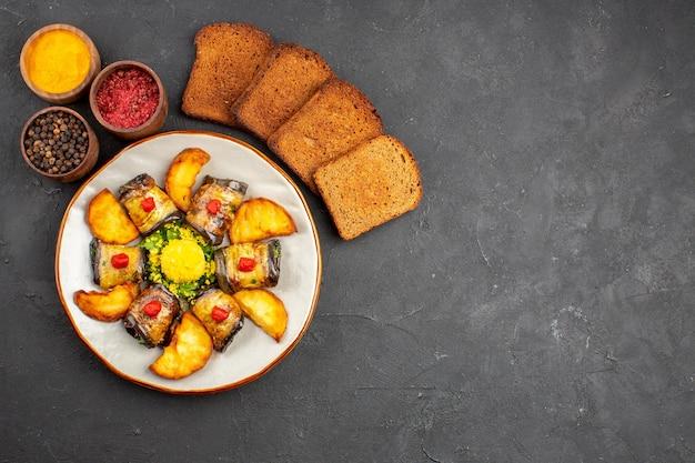 Vista superior deliciosos pãezinhos de berinjela prato cozido com batatas, pão e temperos no fundo escuro prato cozinhar alimentos batata frita assar