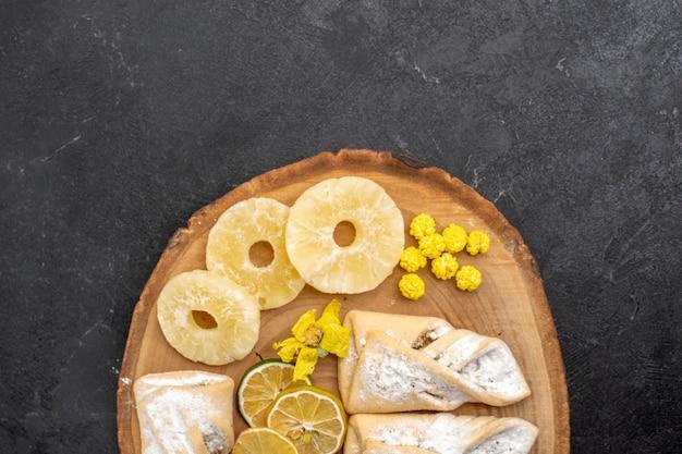 Vista superior deliciosos pastéis com fatias de frutas secas no espaço cinza