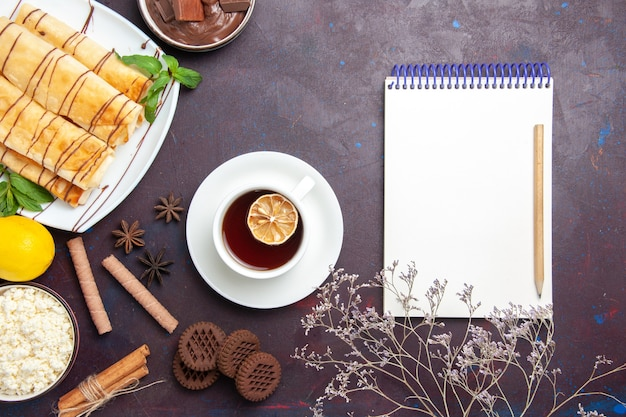 Vista superior deliciosos pastéis doces com biscoitos e chá na mesa escura