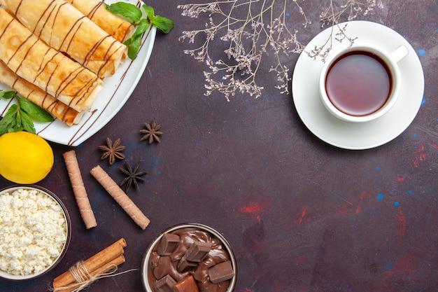 Vista superior deliciosos pastéis doces com limão e xícara de chá no espaço escuro