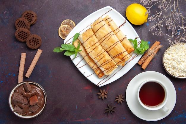 Vista superior deliciosos pastéis doces com xícara de chá e chocolate no espaço escuro
