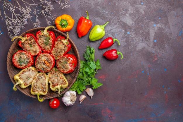 Vista superior deliciosos pimentões assados no prato com recheio de carne e vegetais no fundo escuro.