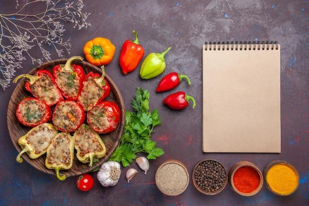 Vista superior deliciosos pimentões assados no prato com recheio picado e vegetais no fundo escuro prato carne jantar assar refeição