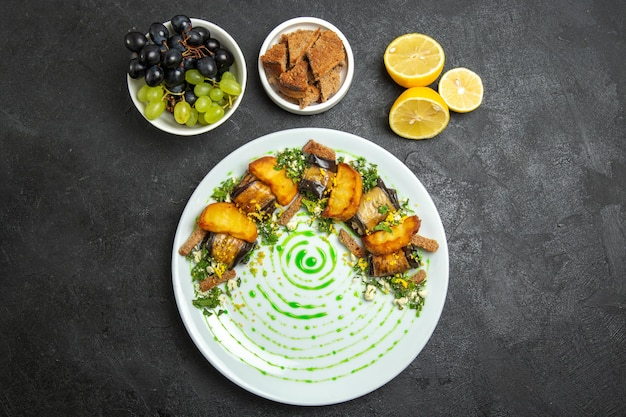 Vista superior deliciosos rolos de berinjela com batatas assadas dentro do prato no fundo escuro prato refeição jantar comida batata vegetal