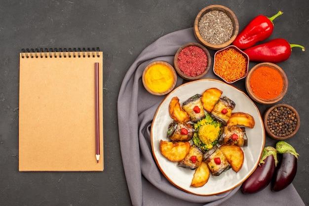 Vista superior deliciosos rolos de berinjela cozidos prato com batatas assadas e temperos na mesa escura prato de refeição de comida cozinha de batata
