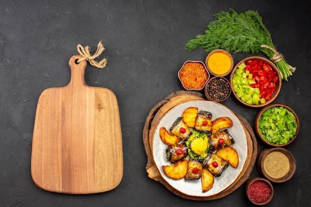 Vista superior deliciosos rolos de berinjela cozidos prato com batatas e temperos na superfície escura prato refeição jantar comida