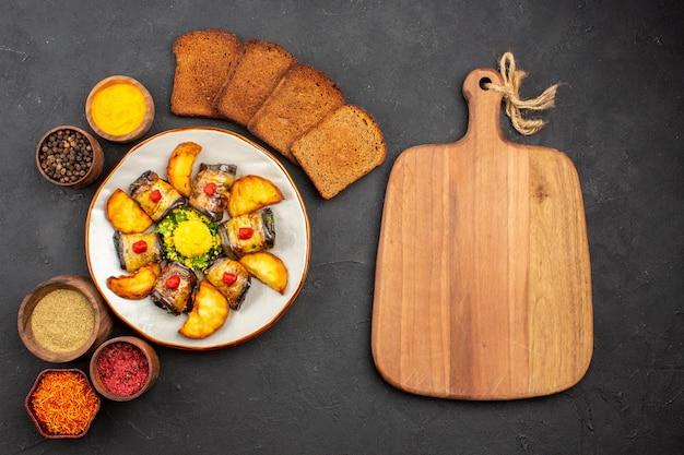 Vista superior deliciosos rolos de berinjela cozidos prato com batatas, pão e temperos em fundo escuro prato cozinhar comida batata frita