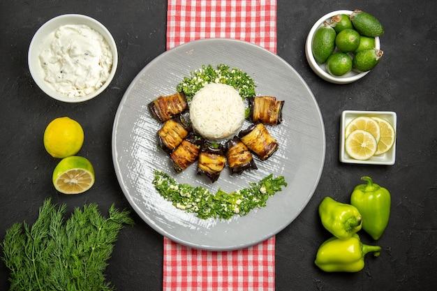 Vista superior deliciosos rolos de berinjela prato cozido com arroz na mesa escura cozinhando arroz óleo vegetal comida