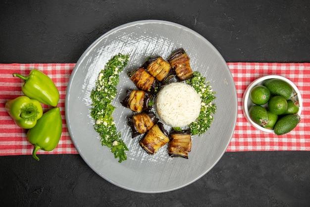 Vista superior deliciosos rolos de berinjela prato cozido com arroz na superfície escura cozinhando arroz óleo vegetal comida