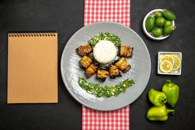 Vista superior deliciosos rolos de berinjela prato cozido com arroz na superfície escura cozinhando arroz óleo vegetal comida Foto gratuita