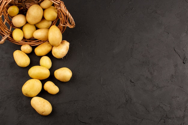 Vista superior descascada batatas inteiras dentro da cesta no chão escuro